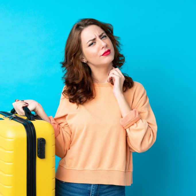 Traveler woman with suitcase over isolated blue background thinking an idea