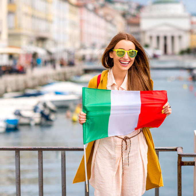 Young female traveler with italian flag standing on the bridge in the centre of Trieste city in Italy. Promoting tourism in Italy